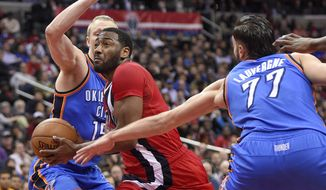 Washington Wizards guard John Wall, center, drives to the basket against Oklahoma City Thunder forward Kyle Singler, left, and center Joffrey Lauvergne (77), of France, during the second half of an NBA basketball game, Monday, Feb. 13, 2017, in Washington. The Wizards won 120-98. (AP Photo/Nick Wass)