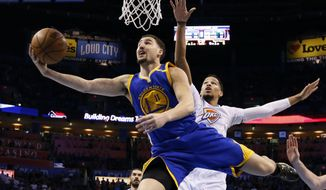 Golden State Warriors guard Klay Thompson (11) shoots in front of Oklahoma City Thunder forward Andre Roberson, right, in the first quarter of an NBA basketball game in Oklahoma City, Saturday, Feb. 11, 2017. (AP Photo/Sue Ogrocki)