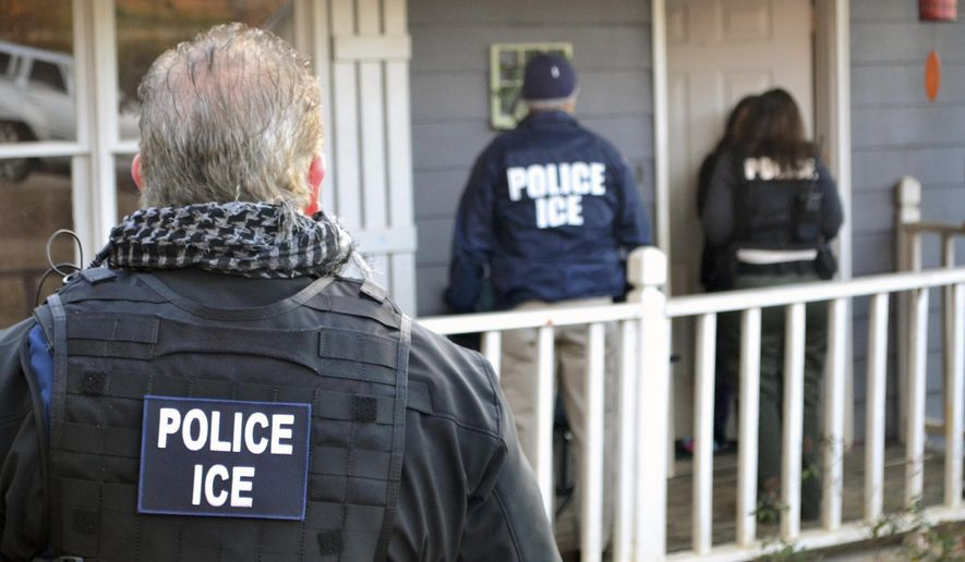 In this Feb. 9, 2017, file photo provided U.S. Immigration and Customs Enforcement, ICE agents at a home in Atlanta, during a targeted enforcement operation aimed at immigration fugitives, re-entrants and at-large criminal aliens. (Bryan Cox/ICE via AP)