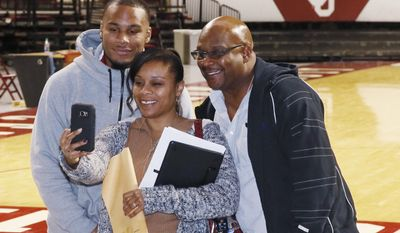 Oklahoma point guard Jordan Woodard, left, poses for a selfie with his mother, Petra Woodard, and his father, Marcus Woodard, right, in front of the Oklahoma basketball court, following a news conference in Norman, Okla., Monday, Feb. 13, 2017. Woodard is out for the season with a torn ACL in his right knee, effectively ending his college career. (AP Photo/Sue Ogrocki)