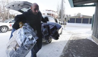 Fadel Alshawwa, Manitoba Interfaith Immigration Council, brings blankets into a community hall for refugees that may walk across the border in Emerson, Manitoba, Thursday, Feb. 9, 2016. Refugees have been crossing into Canada at Emerson and authorities had a town hall meeting in Emerson to discuss their options. (John Woods/The Canadian Press via AP)