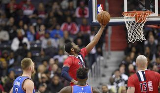 Washington Wizards guard John Wall (2) goes to the basket against Oklahoma City Thunder forward Domantas Sabonis (3), of Lithuania, and guard Anthony Morrow (2) during the first half of an NBA basketball game, Monday, Feb. 13, 2017, in Washington. Also seen is Washington Wizards center Marcin Gortat (13), of Poland. (AP Photo/Nick Wass)