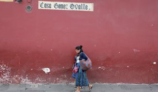 In this photograph taken Dec. 14, 2016, indigenous women walk by a colorfully painted building in Antigua Guatemala, Guatemala. Established in 1543 as the territorial capital of the Spanish crown and abandoned after a series of earthquakes, the colonial city is home to preserved and colorful churches and mansions from the era and now is a tourist center. (AP Photo/Manuel Valdes)