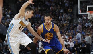 Golden State Warriors guard Stephen Curry, right, drives past Denver Nuggets forward Juancho Hernangomez, of Spain, to the rim in the first half of an NBA basketball game, Monday, Feb. 13, 201, in Denver. (AP Photo/David Zalubowski) **FILE**