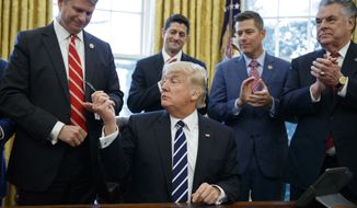 President Donald Trump hands a pen to Rep. Bill Huizenga, R-Mich., after signing House Joint Resolution 41 in the Oval Office of the White House in Washington, Tuesday, Feb. 14, 2017. From left are, Huizenga, Trump, House Speaker Paul Ryan of Wis., Rep. Sean Duffy, R-Wis., and Rep. Peter King, R-N.Y. (AP Photo/Evan Vucci)
