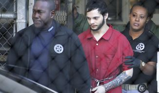 FILE- In this Jan. 30, 2017, file photo, Esteban Santiago, center, is led from the Broward County jail for an arraignment in federal court in Fort Lauderdale, Fla. Santiago, who is accused of killing five people at a Florida airport, lied about his criminal record on his application to be a security guard in Alaska, and was fired after only a few months on the job because of the state of his mental health. The state released the application Monday, Feb. 13, to The Associated Press, which had appealed the state's initial refusal to release the document made through an open records request. (AP Photo/Lynne Sladky, File)