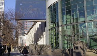 People pass by the Charlotte Convention Center in Charlotte, N.C., Monday, Feb. 13, 2017. Charlotte won't be a ghost town this weekend, but it sure won't be buzzing like many had hoped when the NBA awarded the city the 2017 All-Star game. But the league moved the event last summer after North Carolina politicians decided against repealing House Bill 2, a law that passed last March that restricts the rights of LGBT people. (AP Photo/Chuck Burton)