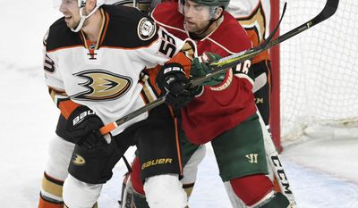 Minnesota Wild's Jason Zucker, right, gets sandwiched between Anaheim Ducks' Shea Theodore, left and Cam Fowler, center, in front of Ducks' goalie John Gibson (35) in the second period of an NHL hockey game, Tuesday, Feb. 14, 2017, in St. Paul, Minn.(AP Photo/Tom Olmscheid)