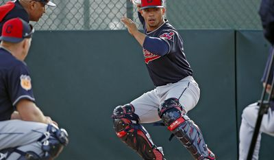 Cleveland Indians catcher Francisco Mejia, right, gets into position to throw the baseball as Sandy Alomar Jr., top left, and Erik Kratz, bottom left, watch at the Indians baseball spring training facility Tuesday, Feb. 14, 2017, in Goodyear, Ariz. (AP Photo/Ross D. Franklin)