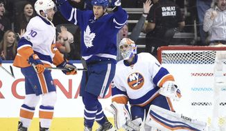 Toronto Maple Leafs left wing Matt Martin (15) celebrates a goal by left wing Josh Leivo (not shown) as New York Islanders goalie Thomas Greiss (1) and centre Alan Quine (10) look on during first period NHL hockey action in Toronto on Tuesday, Feb. 14, 2017. (Frank Gunn/The Canadian Press via AP)