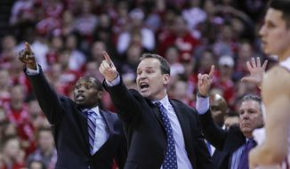 Northwestern coach Chris Collins, center, reacts during the second half of an NCAA college basketball game against Wisconsin, Sunday, Feb. 12, 2017, in Madison, Wis. Northwestern upset Wisconsin 66-59. (AP Photo/Andy Manis)