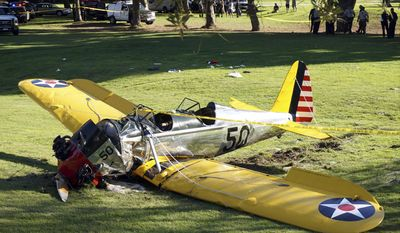 FILE - In this March 5, 2015 file photo, a World War II-era trainer airplane rests on the ground after actor Harrison Ford crash-landed it after reporting engine failure on the Penmar Golf Course in the Venice area of Los Angeles. NBC-TV says Ford had a potentially serious run-in with an airliner at a Southern California airport. NBC reports that Ford, an experienced pilot, was told to land on a runway at John Wayne Airport in Orange County on Monday, Feb. 13, 2017, but mistakenly landed on a parallel taxiway, passing over an American Airlines jet holding nearby. (AP Photo/Damian Dovarganes, File)