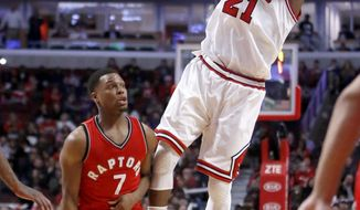 Chicago Bulls' Jimmy Butler (21) shoots after being fouled by Toronto Raptors' Kyle Lowry (7) during the second half of an NBA basketball game Tuesday, Feb. 14, 2017, in Chicago. The Bulls won 105-94. (AP Photo/Charles Rex Arbogast)