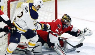 Ottawa Senators goalie Craig Anderson (41) attempts to control the puck as Buffalo Sabres right wing Brian Gionta (12) closes in during the second period of an NHL hockey game Tuesday, Feb. 14, 2017, in Ottawa, Ontario. (Fred Chartrand/The Canadian Press via AP)