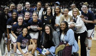 Former and current Connecticut basketball players gather for a team photograph at the end of an NCAA college basketball game against South Carolina, Monday, Feb. 13, 2017, in Storrs, Conn. UConn won their 100th straight game. (AP Photo/Jessica Hill)