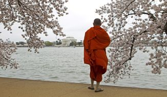 In this March 27, 2016, file photo, a visitor take pictures of cherry blossom trees in full bloom on the tidal basin in Washington, D.C. (AP Photo/Jose Luis Magana, File)