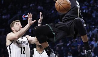Milwaukee Bucks' Giannis Antetokounmpo (34) dunks the ball in front of Brooklyn Nets' Joe Harris (12) and Trevor Booker (35) during the first half of an NBA basketball game, Wednesday, Feb. 15, 2017, in New York. (AP Photo/Frank Franklin II)