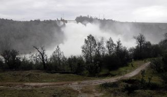 A trail runs along the Feather River as water gushes from the Oroville Dam's main spillway Wednesday, Feb. 15, 2017, in Oroville, Calif. The Oroville Reservoir is continuing to drain Wednesday as state water officials scrambled to reduce the lake's level ahead of impending storms. (AP Photo/Marcio Jose Sanchez)