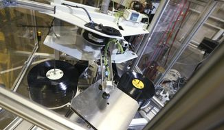 ADVANCE FOR USE SUNDAY, FEB. 19 - In this Jan. 17, 2017, vinyl records sit in an album press at Hand Drawn Pressing in Addison, Texas. (Nathan Hunsinger/The Dallas Morning News via AP)