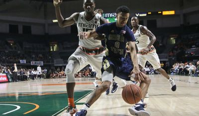 Georgia Tech's Justin Moore (0) loses control of the ball as Miami's Ebuka Izundu defends during the first half of an NCAA college basketball game, Wednesday, Feb. 15, 2017, in Coral Gables, Fla. (AP Photo/Lynne Sladky)
