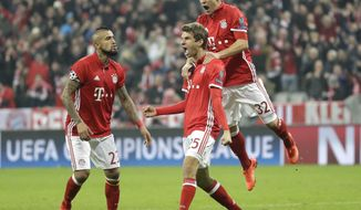 Bayern's Thomas Mueller, center, celebrates with his teammates Joshua Kimmich, right, and Arturo Vidal after scoring his side's fifth goal during the Champions League round of 16 first leg soccer match between FC Bayern Munich and Arsenal, in Munich, Germany, Wednesday, Feb. 15, 2017. (AP Photo/Matthias Schrader)