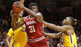 Indiana's Thomas Bryant , left, tries to pass the ball as Minnesota's Reggie Lynch (22) and Akeem Springs, right, defend during the first half of an NCAA college basketball game Wednesday, Feb. 15, 2017, in Minneapolis. (AP Photo/Jim Mone)