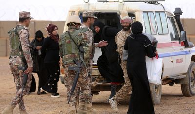 In this Tuesday, Feb. 14, 2017, photo, Syrian patients from the informal, Rukban camp are security cleared by the Tribes Army on the Syrian side of the berm before being transported by Jordanian military to a clinic inside Jordan for a medical check up. Conditions in the camp deteriorated sharply after Jordan sealed its border in June, following a cross-border IS attack that killed seven Jordanian border guards. (AP Photo/ Raad Adayleh)