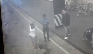 This image provided by Star TV on Wednesday, Feb. 15, 2017, of closed circuit television footage from Monday, Feb 13, 2017, shows a woman, left, at Kuala Lumpur International Airport in Sepang, Malaysia, who police say was arrested Wednesday in connection with the death of Kim Jong Nam, the half brother of North Korean leader Kim Jong Un. (Star TV via AP)
