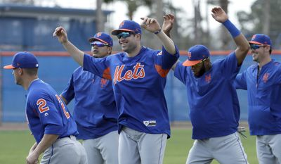 New York Mets second baseman Neil Walker, center, stretches with teammates during a spring training baseball workout Wednesday, Feb. 15, 2017, in Port St. Lucie, Fla. (AP Photo/David J. Phillip)