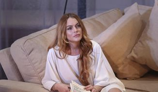 """Actress Lindsay Lohan performs a scene from the play, """"Speed the Plow,"""" during a photocall at the Playhouse Theatre in central London, in this Sept. 30, 2014, file photo. (Photo by Joel Ryan/Invision/AP, File)"""