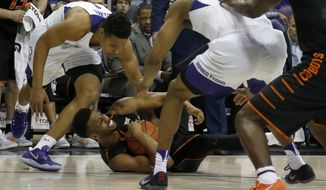 Oklahoma State forward Leyton Hammonds, bottom, scrambles for a loose ball against TCU guard Desmond Bane, left, in the first half of a NCAA college basketball game in Fort Worth, Texas on Wednesday, Feb. 15, 2017. (Brad Loper/Star-Telegram via AP)