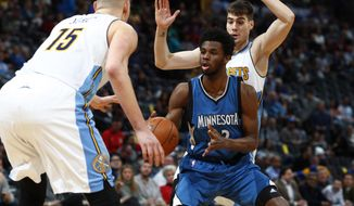 Minnesota Timberwolves forward Andrew Wiggins, center, loses control of the ball as he drives the lane to the rim between Denver Nuggets forwards Nikola Jokic, front, of Serbia, and Juancho Hernangomez, of Spain, in the first half of an NBA basketball game Wednesday, Feb. 15, 2017, in Denver. (AP Photo/David Zalubowski)