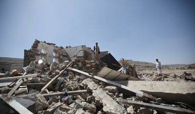 Men stand on the rubble of a house destroyed by a Saudi-led airstrike in the outskirts of Sanaa, Yemen, Thursday, Feb. 16, 2017. At least one Saudi-led airstrike near Yemen's rebel-held capital killed at least five people on Wednesday, the country's Houthi rebels and medical officials said. (AP Photo/Hani Mohammed) ** FILE **