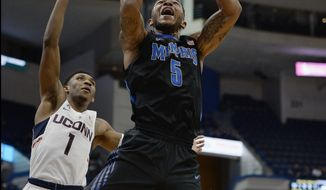 Memphis' Markel Crawford shoots a basket as Connecticut's Christian Vital, left, defends and Connecticut's Jalen Adams, right, looks on, in the first half of an NCAA college basketball game, Thursday, Feb. 16, 2017, in Hartford, Conn. (AP Photo/Jessica Hill)