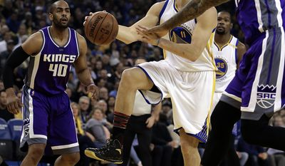 Golden State Warriors' Klay Thompson (11) drives the ball between Sacramento Kings' Arron Afflalo (40) and DeMarcus Cousins, right, during the first half of an NBA basketball game Wednesday, Feb. 15, 2017, in Oakland, Calif. (AP Photo/Ben Margot)