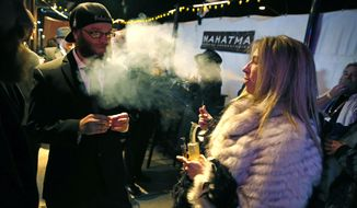 In this Dec. 31, 2013, file photo, partygoers smoke marijuana during a Prohibition-era themed New Year's Eve invite-only party celebrating the start of retail pot sales, at a bar in Denver. Colorado is on the brink of becoming the first state with licensed pot clubs. Denver officials are working on regulations to open a one-year pilot of bring-your-own marijuana clubs. (AP Photo/Brennan Linsley, File)