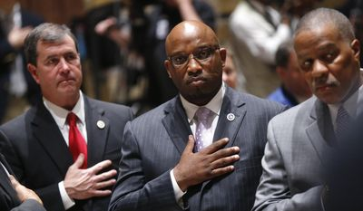 FILE - In this Feb. 13, 2017 file photo, Louisiana State Sen. Troy Brown, D-Geismar, center, holds his hand to his chest during the national anthem at the opening of a special session of the state legislature in Baton Rouge, La. Brown stepped down from his position Thursday, Feb. 16, a day after senators moved ahead with historic expulsion proceedings. Brown pleaded no contest twice over the past year to misdemeanor charges involving abuse against women. (AP Photo/Gerald Herbert, Pool, File)