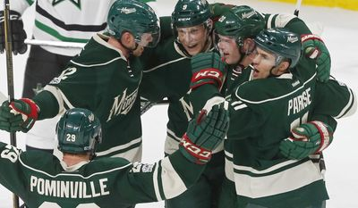 Minnesota Wild players celebrate a power-play goal by Ryan Suter, second from right, off Dallas Stars goalie Kari Lehtonen during the first period of an NHL hockey game Thursday, Feb. 16, 2017, in St. Paul, Minn. (AP Photo/Jim Mone)