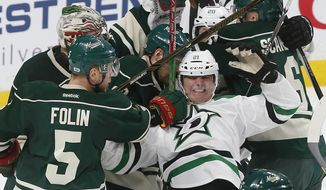 Dallas Stars' Antoine Roussel, right, of France, gets tangled up in a scrum including Minnesota Wild's Christian Folin, left of Sweden, during the second period of an NHL hockey game Thursday, Feb. 16, 2017, in St. Paul, Minn. (AP Photo/Jim Mone)