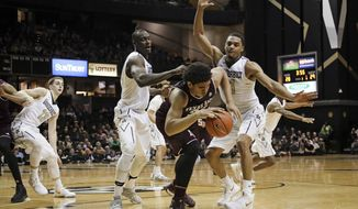 Texas A&M center Tyler Davis is caught between Vanderbilt center Djery Baptiste, left center, and forward Jeff Roberson, right, in the first half of an NCAA college basketball game Thursday, Feb. 16, 2017, in Nashville, Tenn. (AP Photo/Mark Humphrey)