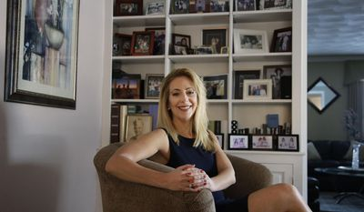 In this Tuesday, Feb. 14, 2017 photo former Tiffany & Co. employee Lisa O'Rourke sits for a portrait in her home in North Kingstown, R.I. O'Rourke said the jewelry retailer pushed her out of the company after she had her breasts and ovaries removed to avoid getting cancer. O'Rourke alleges in a federal lawsuit she was discriminated against after she had the surgeries following a genetic test that found she carried a gene associated with breast cancer. (AP Photo/Steven Senne)