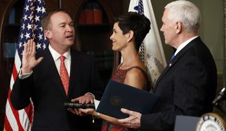 Vice President Mike Pence swears in Mick Mulvaney as Director of Office of Management and Budget in the White House complex in Washington, Thursday, Feb. 16, 2017, as Pamela West Mulvaney holds the Bible. (AP Photo/Pablo Martinez Monsivais)