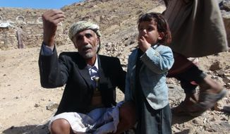This undated handout photo from the Al-Karama Foundation, a Geneva-based non-governmental human rights organization, shows Abdullah Mabkhout al-Ameri, left, next to a child, in Yakla, Yemen. Al-Ameri and several family members including a son who belonged to al-Qaida were killed in a Jan. 29, 2017, US raid in the village. The raid, which left at least 25 Yemenis dead and a US Navy Seal, showed how difficult it is to tell who is al-Qaida in a country where the militants are mingled with tribes and are fighting on the same side as the government against the rebels. (Farouk al-Sharani, Al-Karama Foundation, via AP)