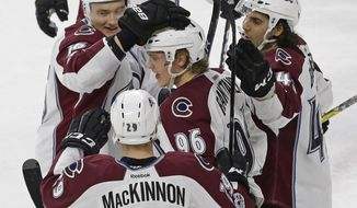 Colorado Avalanche's Mikko Rantanen (96), of Finland, is congratulated by Nikita Zadorov (16), of Russia, Mark Barberio, right, and Nathan MacKinnon (29) following Rantanen's goal against the Carolina Hurricanes during overtime in an NHL hockey game in Raleigh, N.C., Friday, Feb. 17, 2017. Colorado won 2-1. (AP Photo/Gerry Broome)