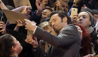 Actor Hugh Jackman poses with fans on the red carpet for the film 'Logan' at the 2017 Berlinale Film Festival in Berlin, Germany, Friday, Feb. 17, 2017. (AP Photo/Michael Sohn)
