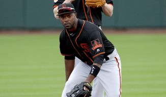 San Francisco Giants' Jimmy Rollins fields a ball as teammate Gordon Beckham watches during a spring training baseball workout, Friday, Feb. 17, 2017, in Scottsdale, Ariz. (AP Photo/Matt York)