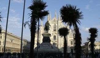 Palm trees are planted in flowerbed in front of Milan's gothic-era Duomo Cathedral, Italy, Friday, Feb. 17, 2017. The appearance of a palm-filled oasis opposite the Duomo has spawned a vibrant public debate ranging from the ironic to the xenophobic. (AP Photo/Antonio Calanni)