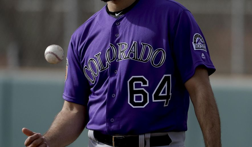 Colorado Rockies relief pitcher Rayan Gonzalez tosses a ball in the air during spring baseball practice in Scottsdale, Ariz., Friday, Feb. 17, 2017. (AP Photo/Chris Carlson)