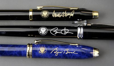 In this Tuesday, Feb. 14, 2017, photo A.T. Cross Co. custom-made pens designed for President Donald Trump, top, former President Barack Obama, center, and former President George W. Bush, below, featuring their signatures and presidential seals, rest side by side at the Cross Company Store in Providence, R.I. (AP Photo/Steven Senne)