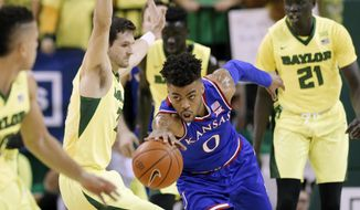 Kansas guard Frank Mason III (0) reaches out to secure a rebound in front of Baylor's Jake Lindsey, center left, and Nuni Omot (21) in the first half of an NCAA college basketball game, Saturday, Feb. 18, 2017, in Waco, Texas. (AP Photo/Tony Gutierrez)